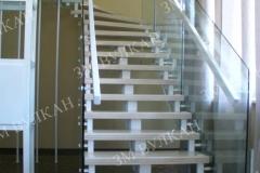 Лестница на металлическом каркасе с деревянными ступенями и стеклянными ограждениями изготовлена и установлена для частного загородного дома