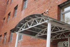 Полукруглый навес над входом из поликарбоната и стали.