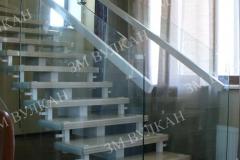 Лестница из металла, дерева и стекла со стеклянными ограждениями установлена внутри частного дома